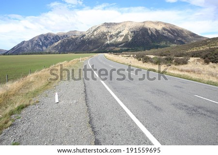 One beautiful road with alpine mountain background in the countryside of New zealand in Autumn season. - stock photo