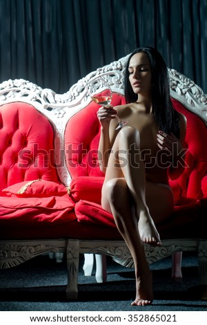 One beautiful sexual naked brunette young woman with straight slim body and long hair holding wine glass sitting indoor in studio on red classic couch on dark background, vertical picture - stock photo