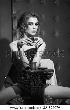 One beautiful sexy sensual young woman with bright makeup and curly hair in dress near column holding coffee cup sitting in studio on leather black background, vertical picture