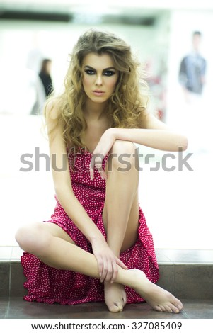 One beautiful straight young blonde woman model with bright makeup and curly hair in red dress sitting barefoot on stairs in shop on light background, vertical picture - stock photo