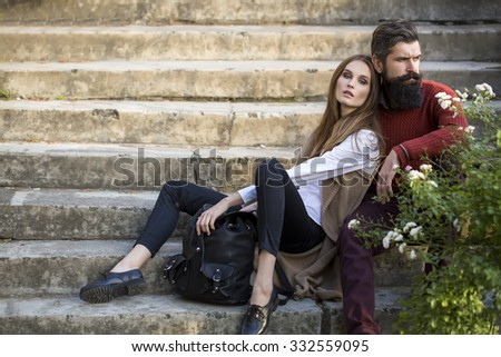 One beautiful stylish couple of young woman and senior man with long black beard sitting embracing close to each other outdoor in autumn street on stairs sunny day, horizontal picture - stock photo