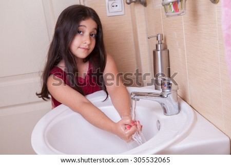 one beautiful 7-8 years middle eastern arab girl with red dress is washing her hands in the bathroom. looking at camera with smile. Developed from RAW. retouched with special care and attention.