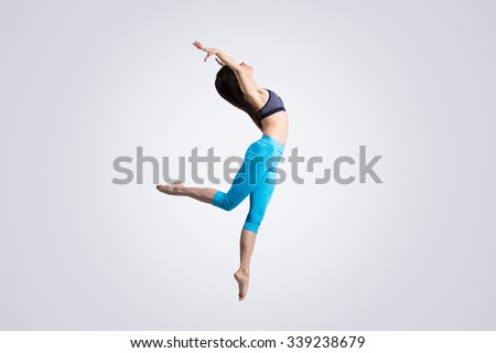 One beautiful young fit modern dancer lady in blue sportswear warming up, working out, dancing and jumping, full length, studio image on gray background - stock photo
