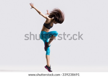 One beautiful young fit modern dancer lady in blue sportswear warming up, working out, dancing and jumping with her long hair flying, full length, studio image on gray background