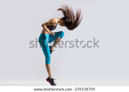 One beautiful young fit modern dancer lady in blue sportswear warming up, working out, dancing with her long hair flying, full length, studio image on gray background - stock photo