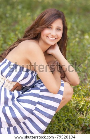 one beautiful young teenage girl wearing a pretty dress outdoors.
