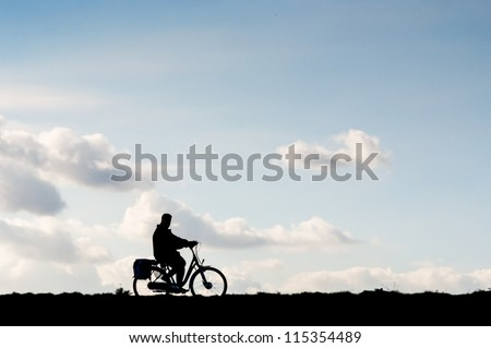 One bicyclist is riding alone on a dike in the Netherlands. - stock photo