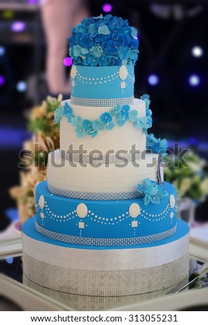 One big beautiful tasty many-tier decorated wedding cake white and blue colours with flower garlad and hydrangea bouquet on top, vertical picture - stock photo