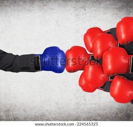One Big Blue glove vs the several of red boxing gloves.  - stock photo
