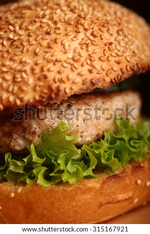 One big delicious appetizing fresh burger of green lettuce leaf cheese meat cutlet and white bread bun with sesame seeds closeup, vertical picture - stock photo