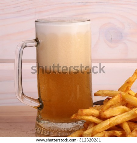One big glass bocal of light cold delicious beer with white froth and tasty crispy yellow potato fasfood chips on wooden background closeup, square picture - stock photo