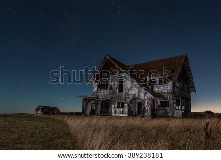 One big old house that is very run down at night. - stock photo