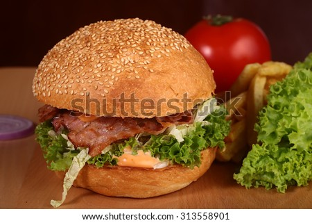 One big tasty appetizing fresh burger of green lettuce red tomato cheese bacon slice meat cutlet violet oinion and white bread bun with sesame seeds on wooden table closeup, horizontal picture