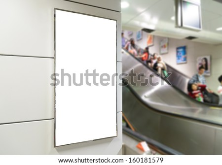 One big vertical / portrait orientation blank billboard in public transport with escalator and blurred passenger background - stock photo