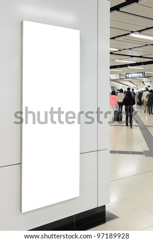 One big vertical / portrait orientation blank billboard on modern white wall with subway concourse and passenger background - stock photo