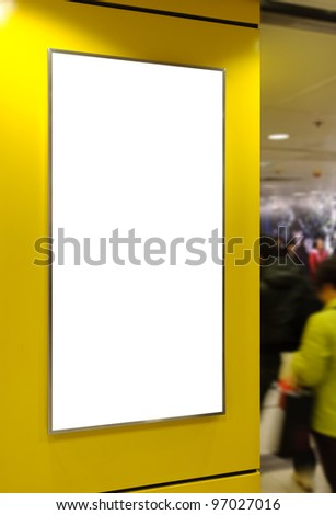 One big vertical / portrait orientation blank billboard on modern yellow wall with sport light and blued passenger background - stock photo