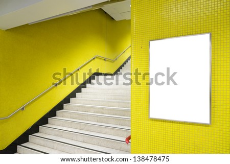 One big vertical / portrait orientation blank billboard on yellow wall with stair background