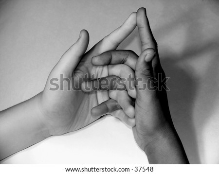 "One black and one white hand  illlustrating children's game: ""Here is the church, here is the steeple, open the doors and see all the people."" - stock photo"