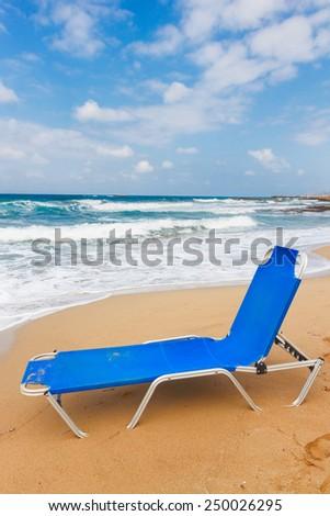 one blue chair on Malia beach, Crete, Greece - stock photo