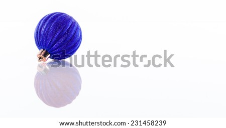 One blue Christmas ball isolated on white reflective perspex background with copy space - stock photo