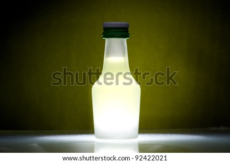 one bottle with lemon liqueur against a green background ,white shine on the ground