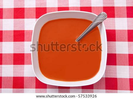 one bowl of tomato soup against a classic traditional red and white checker background - stock photo