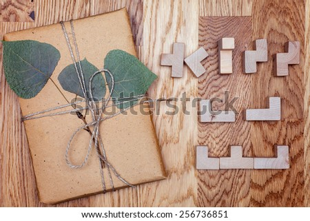 One box in eco paper on the wooden table. Top view. Parcels or gift tied with twine. Green twig lies on the gift. - stock photo