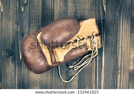 One boxing glove laying on wood grunge background - stock photo