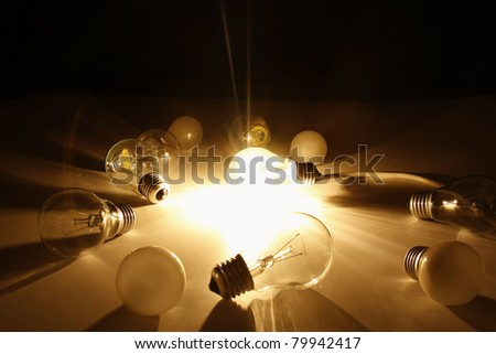One bright lighting bulb among others, closeup - stock photo