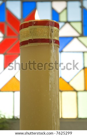 one bright wax candle in color church - stock photo