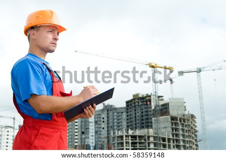 One builder worker with clipboard inspecting works at construction site - stock photo