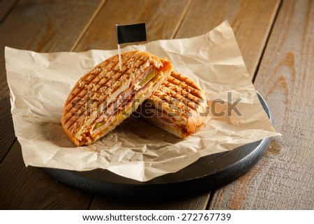 One burger with ham, onion, cucumber and cheese on a wooden plate sprinkled with sesame seeds, paper napkins, small black flag, on a brown wooden background, close-up - stock photo