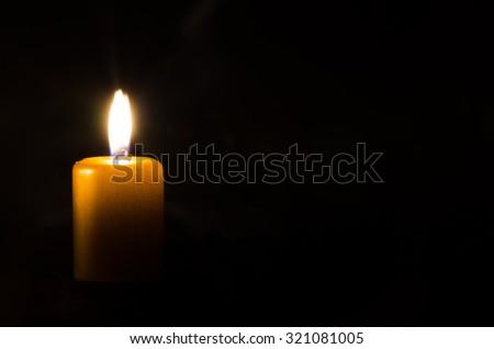 one burning candle decoration against black background - stock photo