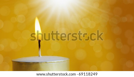one burning candle with bright white light and orbs - stock photo