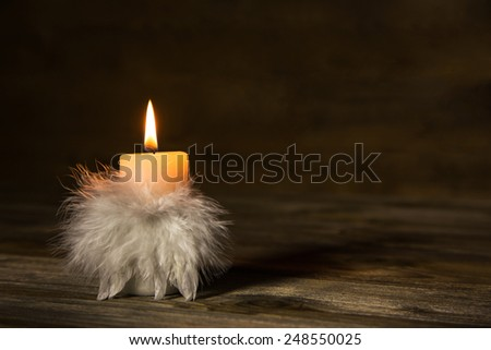One burning candle with feathers on old wooden background. - stock photo