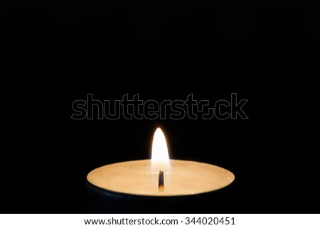 One burning tealight in darkness, closeup - stock photo