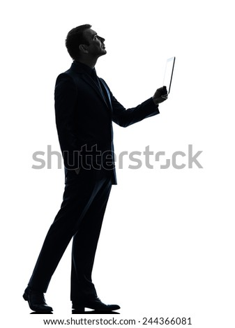 one  business man holding digital tablet looking up in silhouette on white background - stock photo