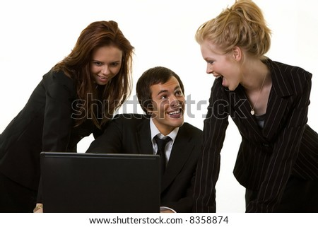 One business man sitting at desk in front of a computer with two woman coworkers standing behind him
