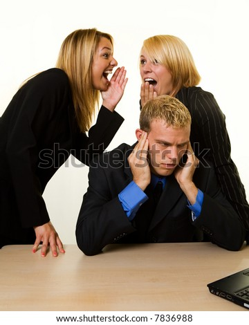 One business man with hands covering hears sitting at desk with two woman coworkers talking behind his back