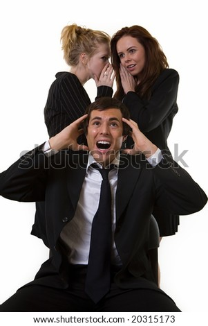 One business man with hands up and upset expression sitting at desk with two woman coworkers talking behind his back - stock photo