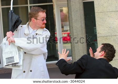 One businessman attacking another with an umbrella - stock photo
