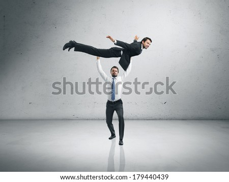 One businessman lifting the second one and helping him to fly - stock photo