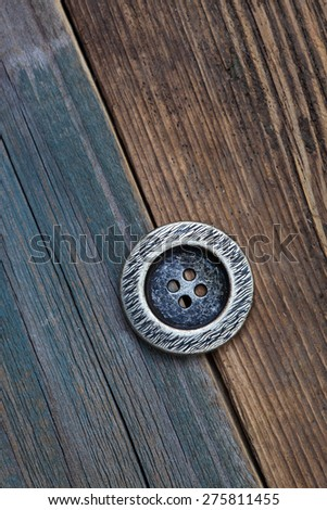 one Button for clothes on an old wooden surface of board