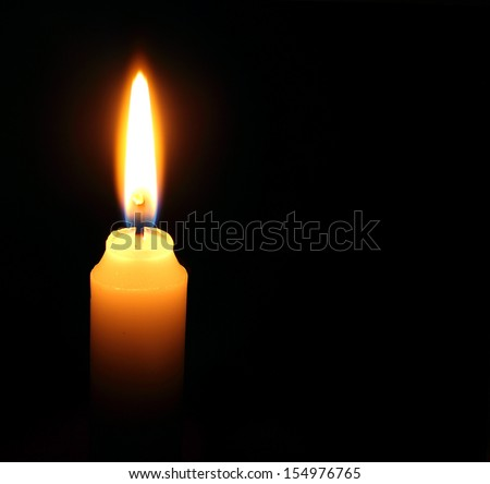 One candle burning brightly in the dark.  - stock photo