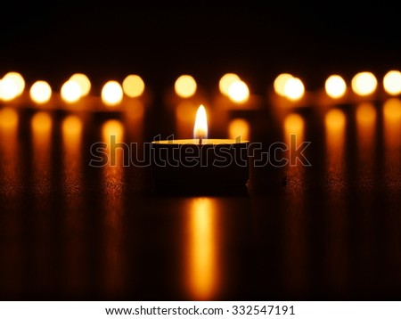 One candle flame at night with bokeh - stock photo