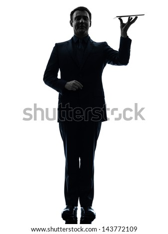 one caucasian business man holding digital tablet   in silhouette on white background - stock photo