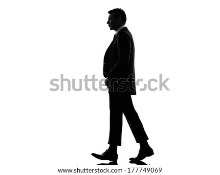 one caucasian business man lifting his pants walking in silhouette on white background