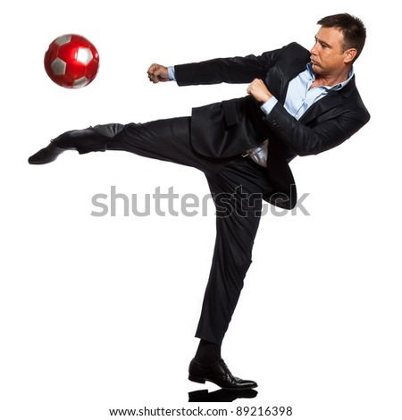 one caucasian business man playing kicking soccer ball in studio isolated on white background - stock photo