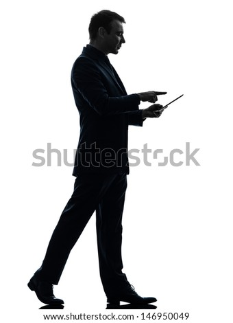 one caucasian business man walking touchscreen digital tablet   in silhouette on white background