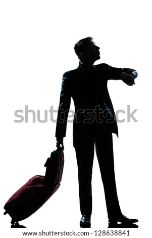 one caucasian  business traveler man checking the time full length silhouette in studio isolated on white background